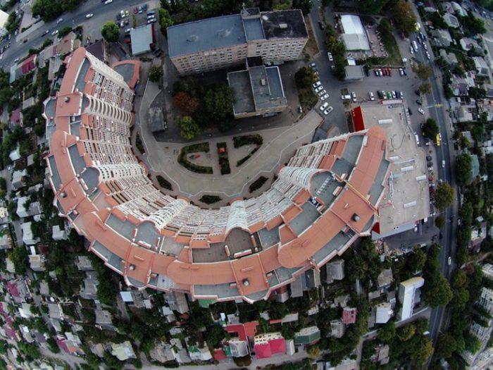 Вид сверху на большой дом, построенный в форме подковы.